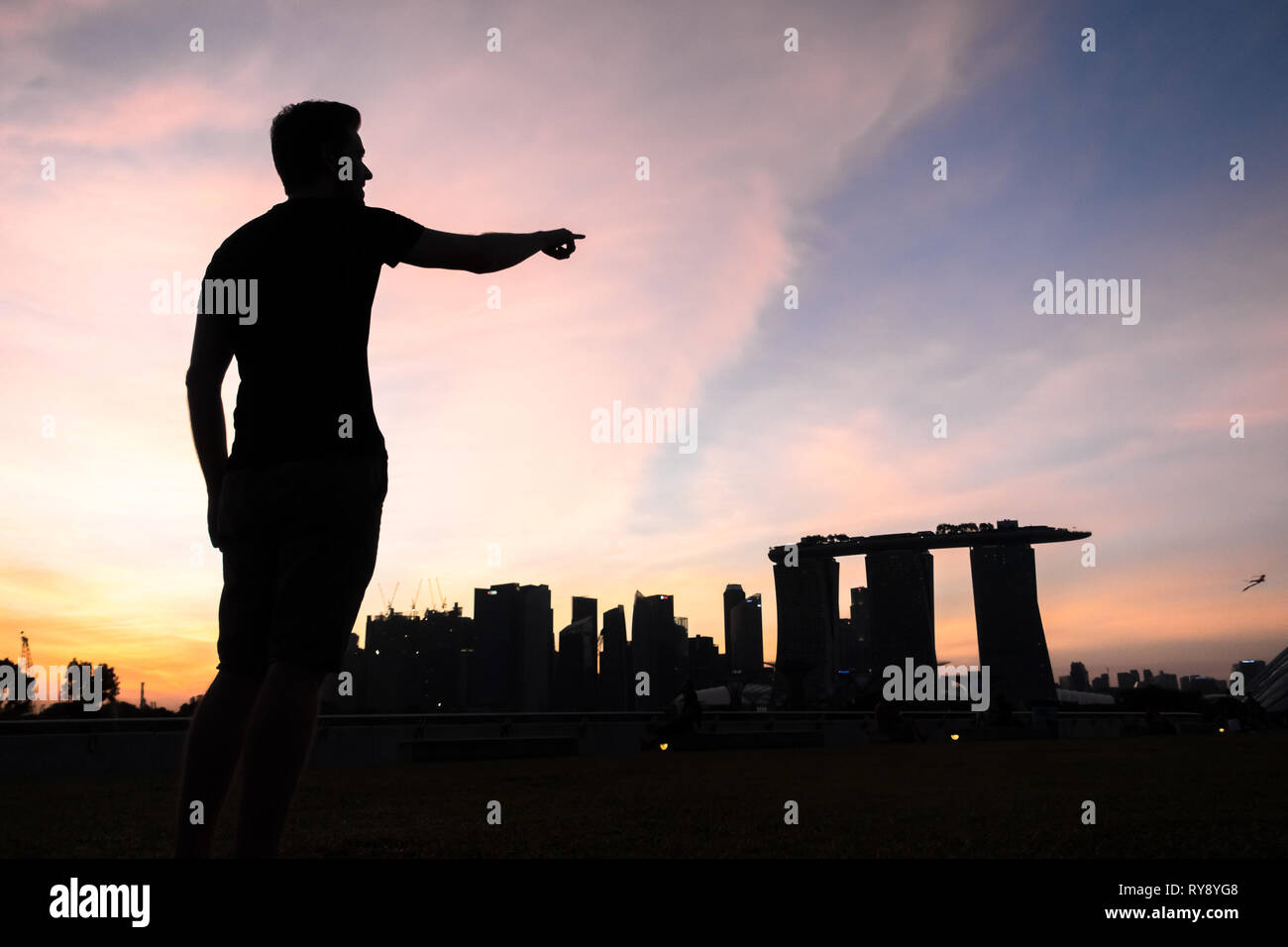 Tourist man silhouette at Marina Barrage, With Sunset Skyline - Singapore - Stock Image