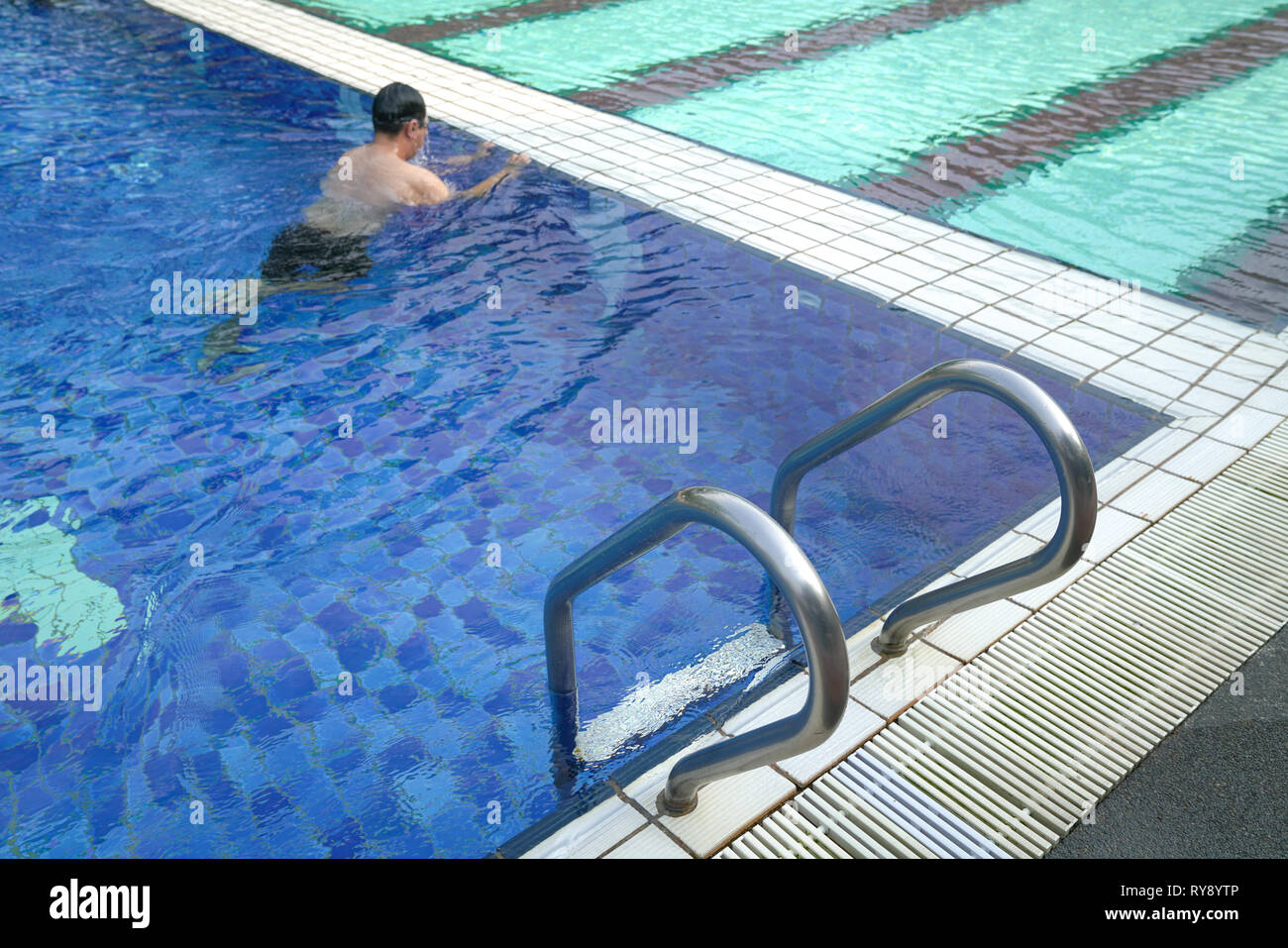 Sports or recreation icons or concept : swimming pool with stair or steps and a swimmer at the background - Stock Image