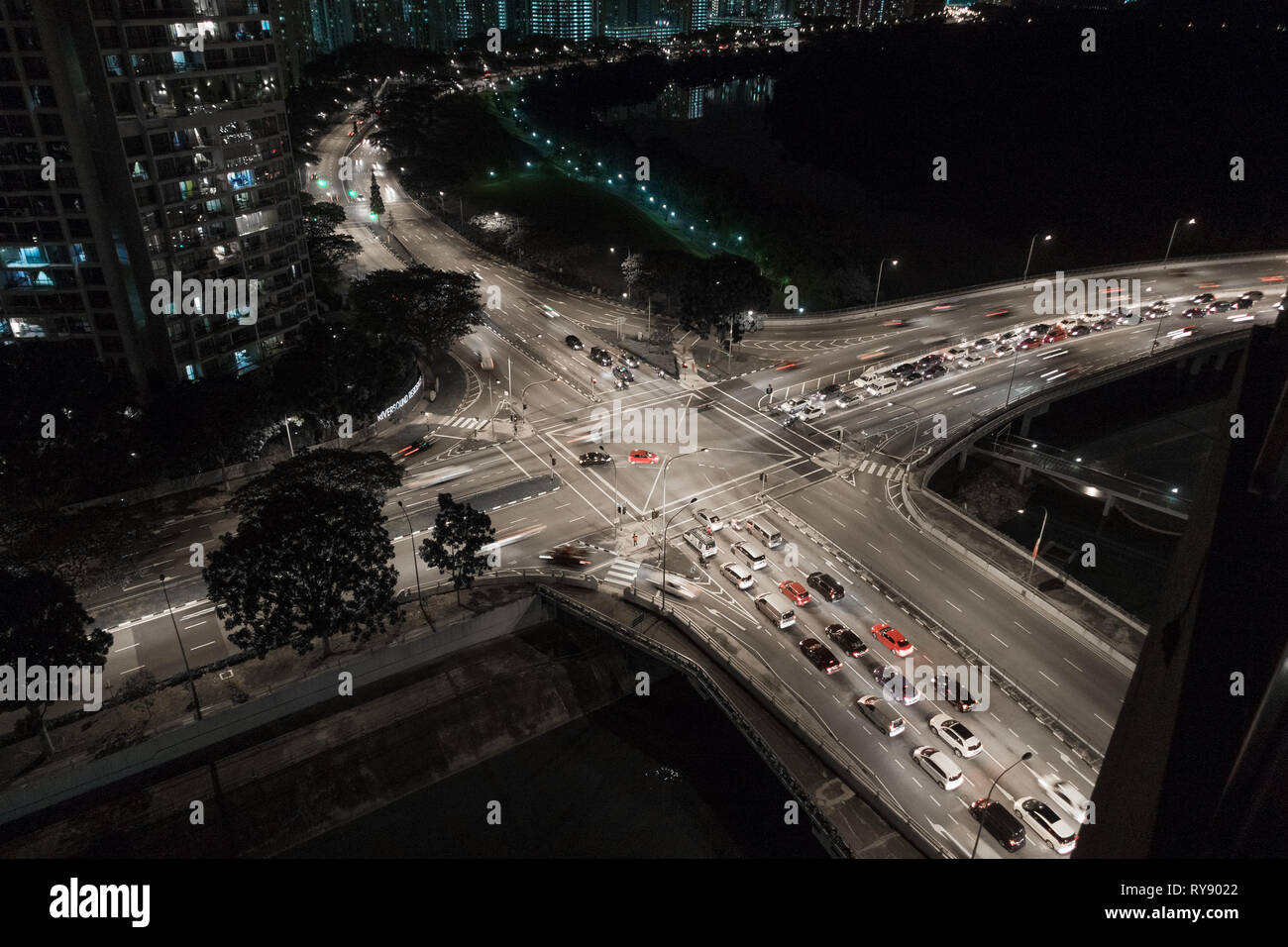 Busy 4 way road intersection, with night time car traffic - Upper Serangoon, Singapore - Stock Image