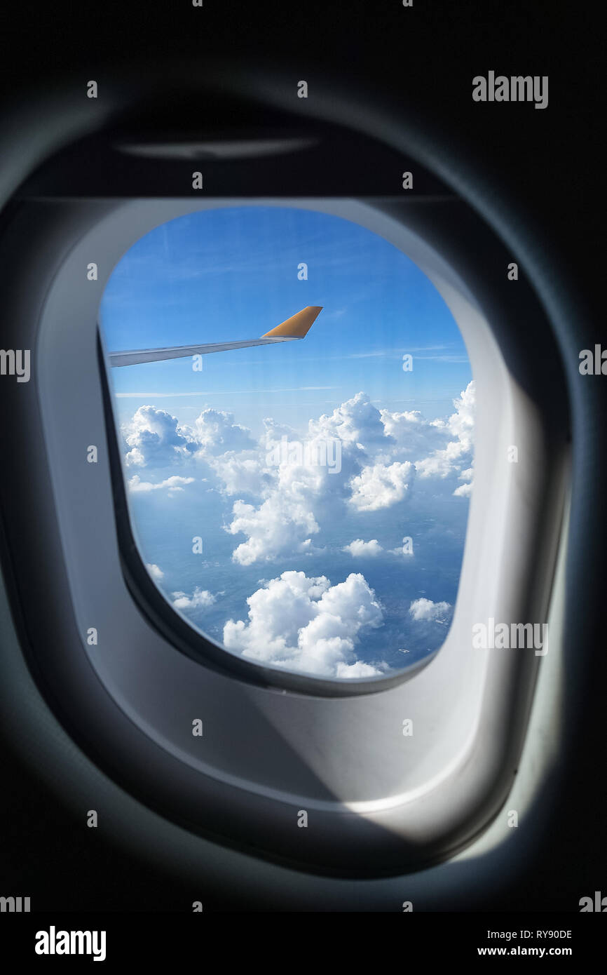 Perfect fluffy clouds out the plane window on sunny, blue sky day - Stock Image
