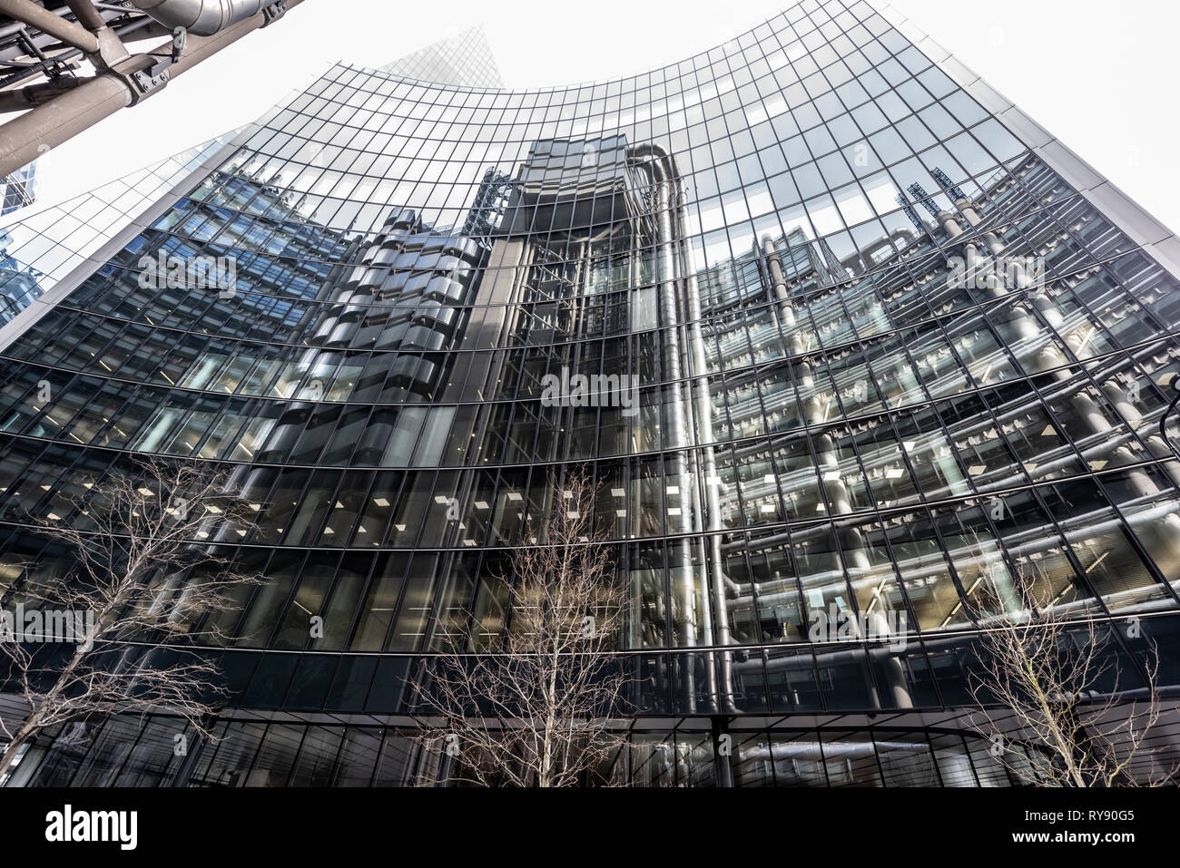 Mirror, mirror on the wall: the refinery-like Lloyds building reflected in the glass curtainwall of the Willis Building on Lime Street - Stock Image