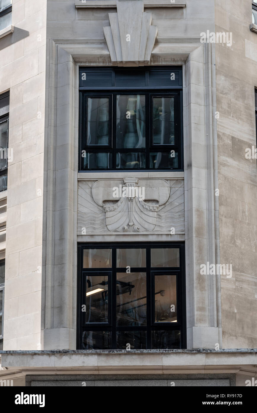An ship carving on the face of an Art deco building in Fenchurch Avenue. - Stock Image