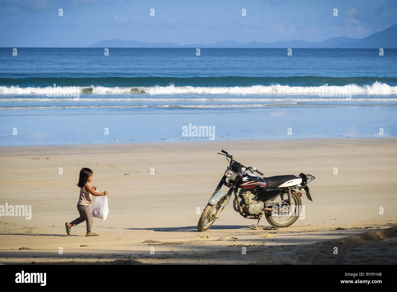 Little Filipino girl hangs a bag a bag on an old motorcycle in the sand - San Vicente Long Beach, Palawan - Philippines - Stock Image
