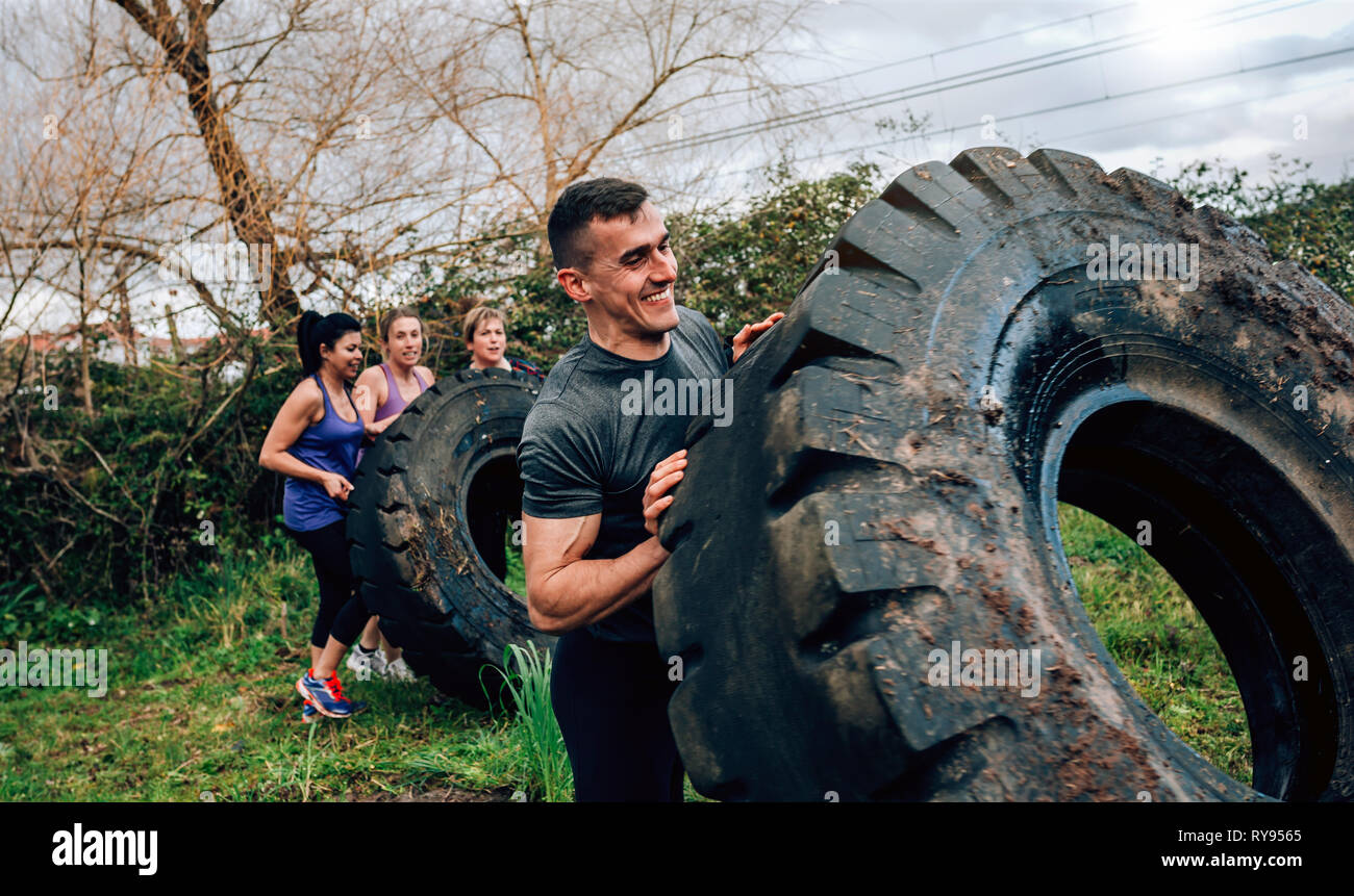 Participant in an obstacle course turning wheel Stock Photo