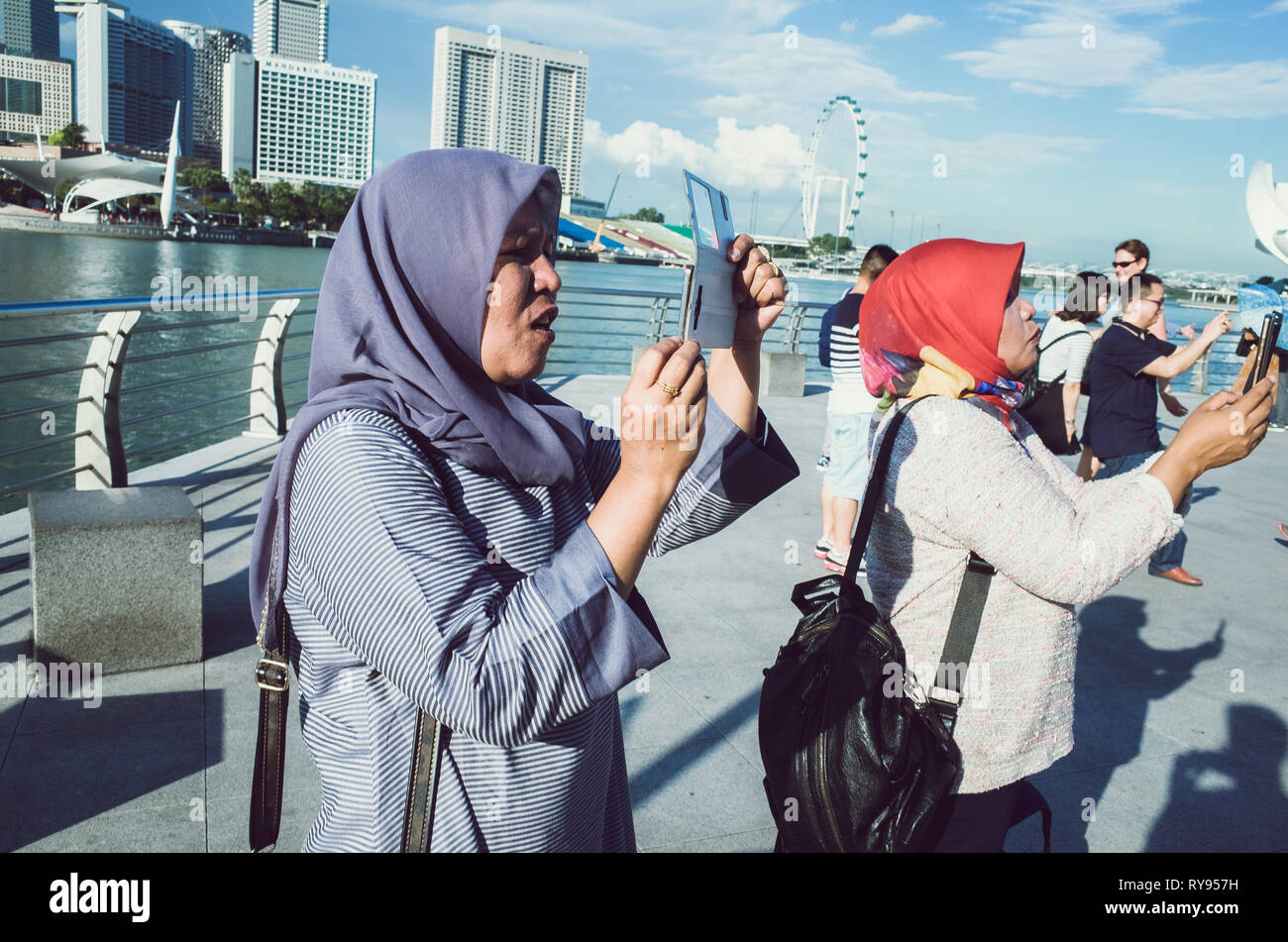 Muslim tourist women in purple and red hijabs, taking vacation photos at Marina Bay, Singapore - Stock Image