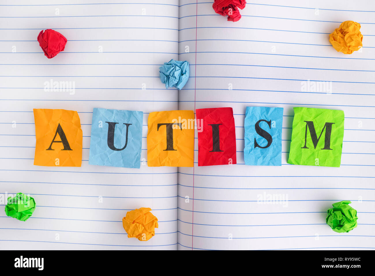 Autism. Word Autism on notebook sheet with some colorful crumpled paper balls around it. Close up. - Stock Image