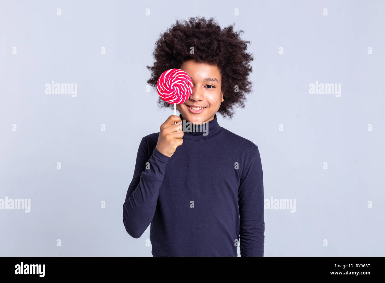 Beaming curly young guy closing his face with sweet red candy - Stock Image