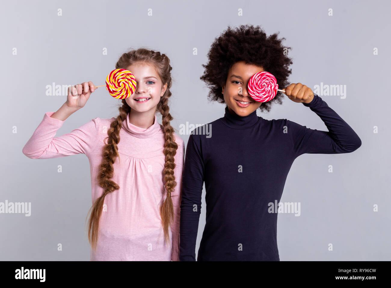 Smiling beaming kids wearing turtlenecks while making photos - Stock Image
