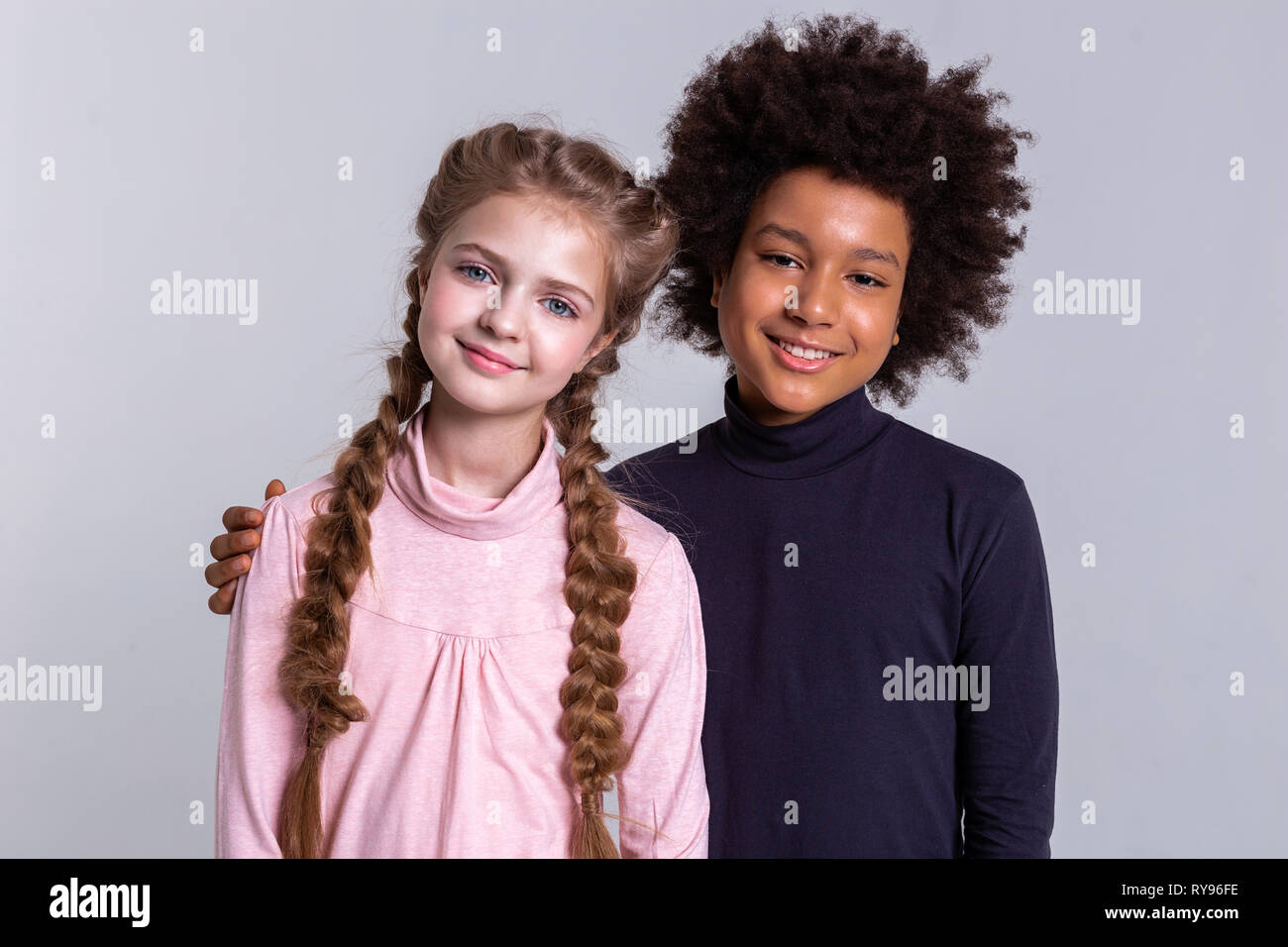 Smiling African American boy gently hugging his blonde friend - Stock Image