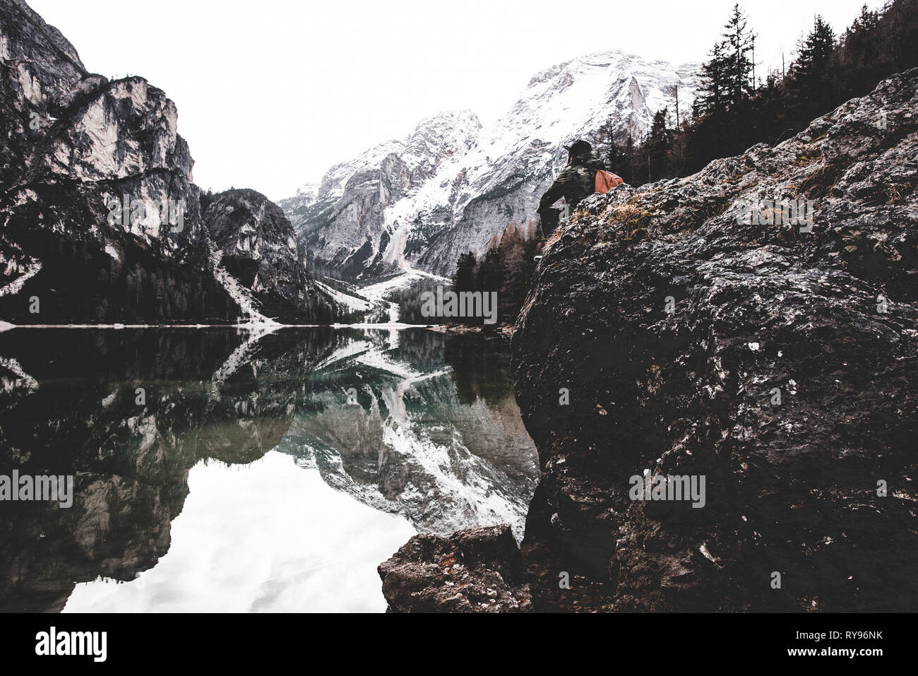 Side view of male sitting on rock near amazing lake and high mountains in Italy - Stock Image