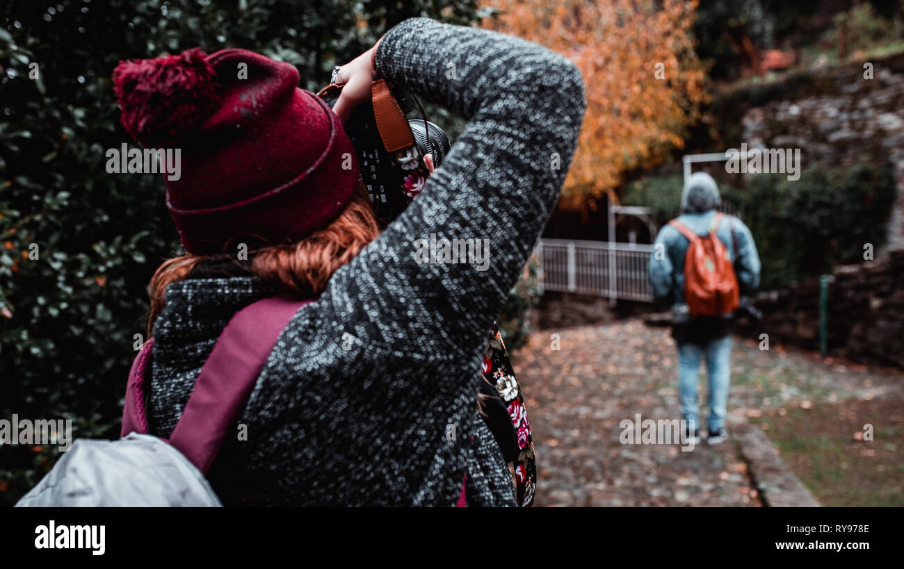 Back view of lady taking photo of male with backpack on professional camera in garden between fallen leaves on way in Italy - Stock Image