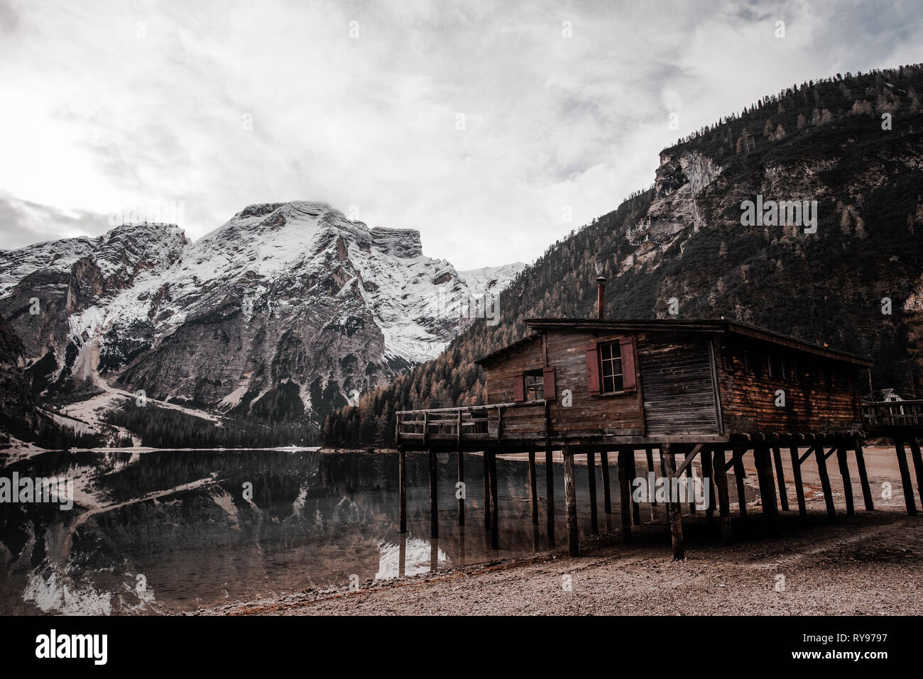 Wooden cabin on stilts on coast near amazing lake and stone high mountains and cloudy sky in Italy - Stock Image