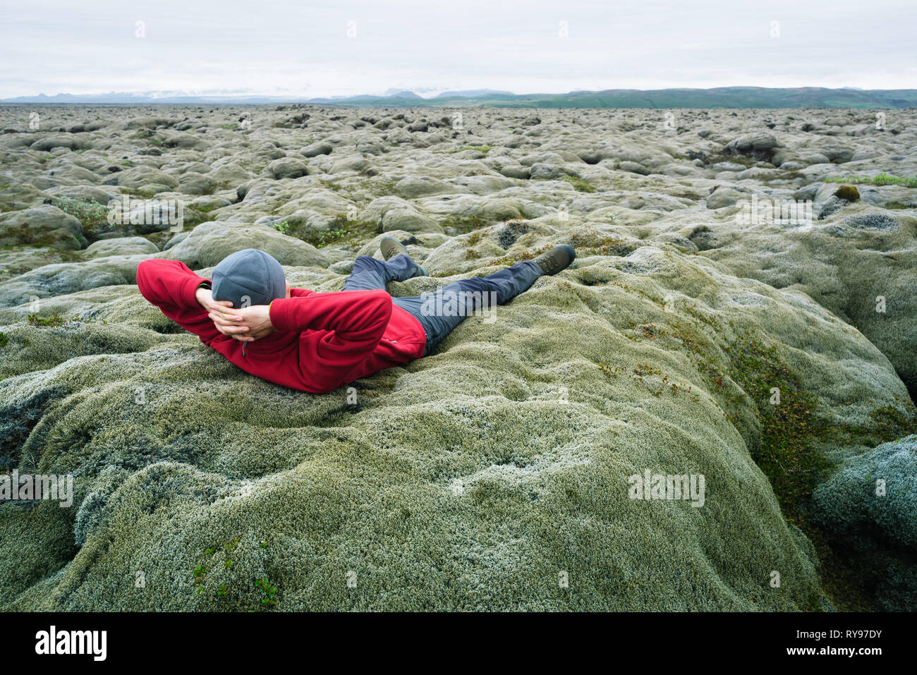 Man traveler in red jacket lying on the moss. Lava field on the south coast of Iceland, Europe. Tourist attraction. Amazing in nature. Cloudy summer d - Stock Image