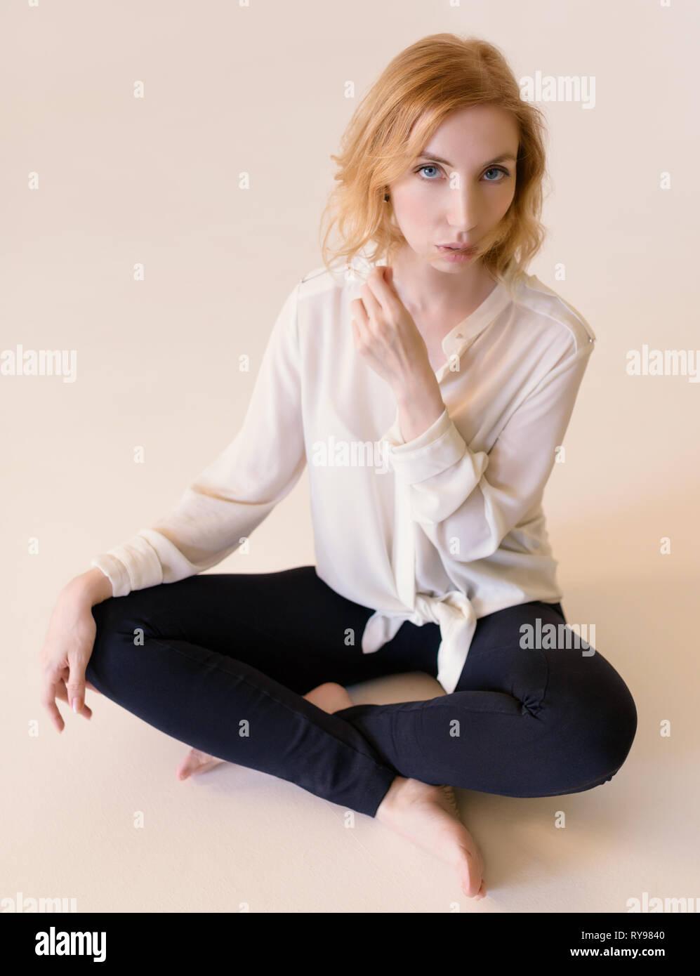Beautiful woman in black leggings on beige background. - Stock Image