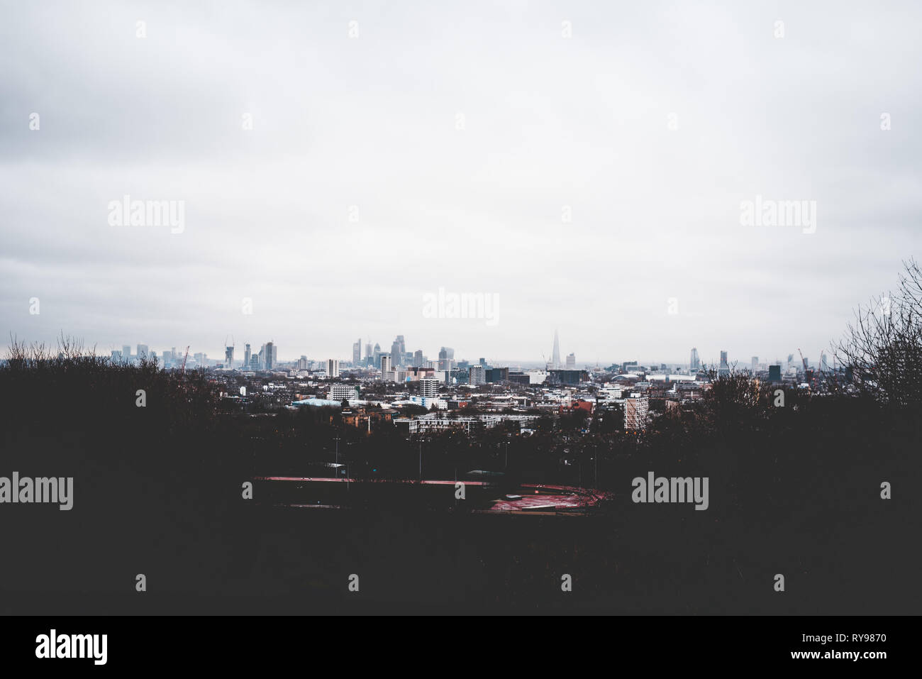 Panorama of murk London with high skyscrapers and cloudy heaven - Stock Image