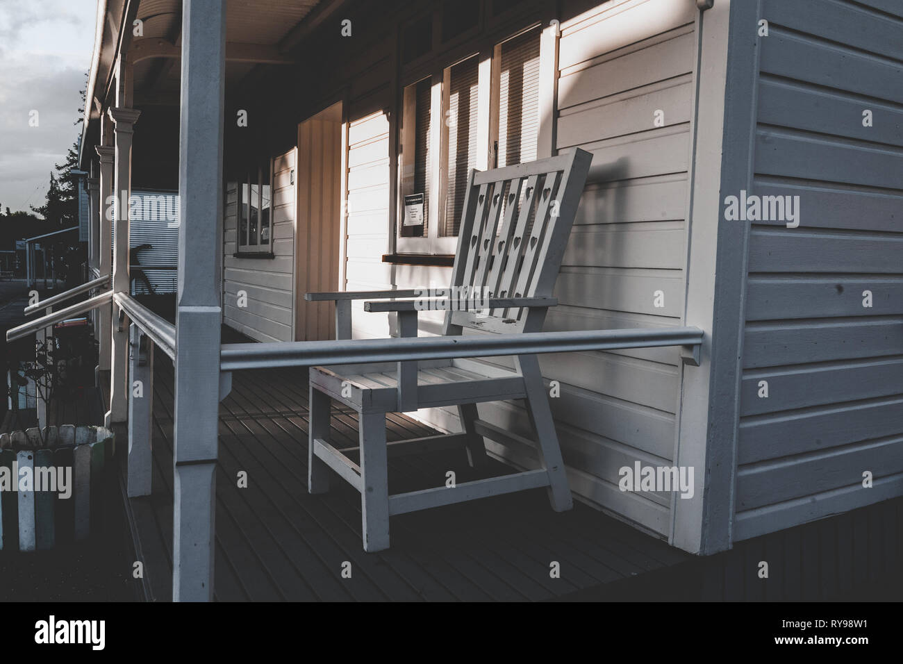 Wooden chair on porch of cottage in sunny day in west neighborhood - Stock Image
