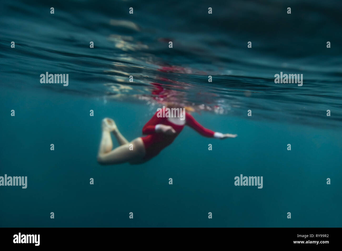Side view of female in red swimsuit diving in blue water of sea on Bali, Indonesia - Stock Image
