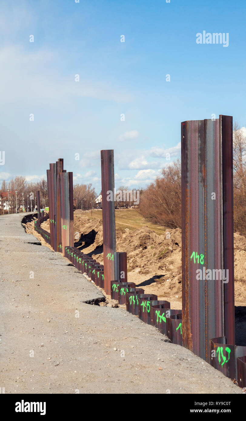 Steel pillar hitting in the ground to stabilizes the flood protection dam Stock Photo