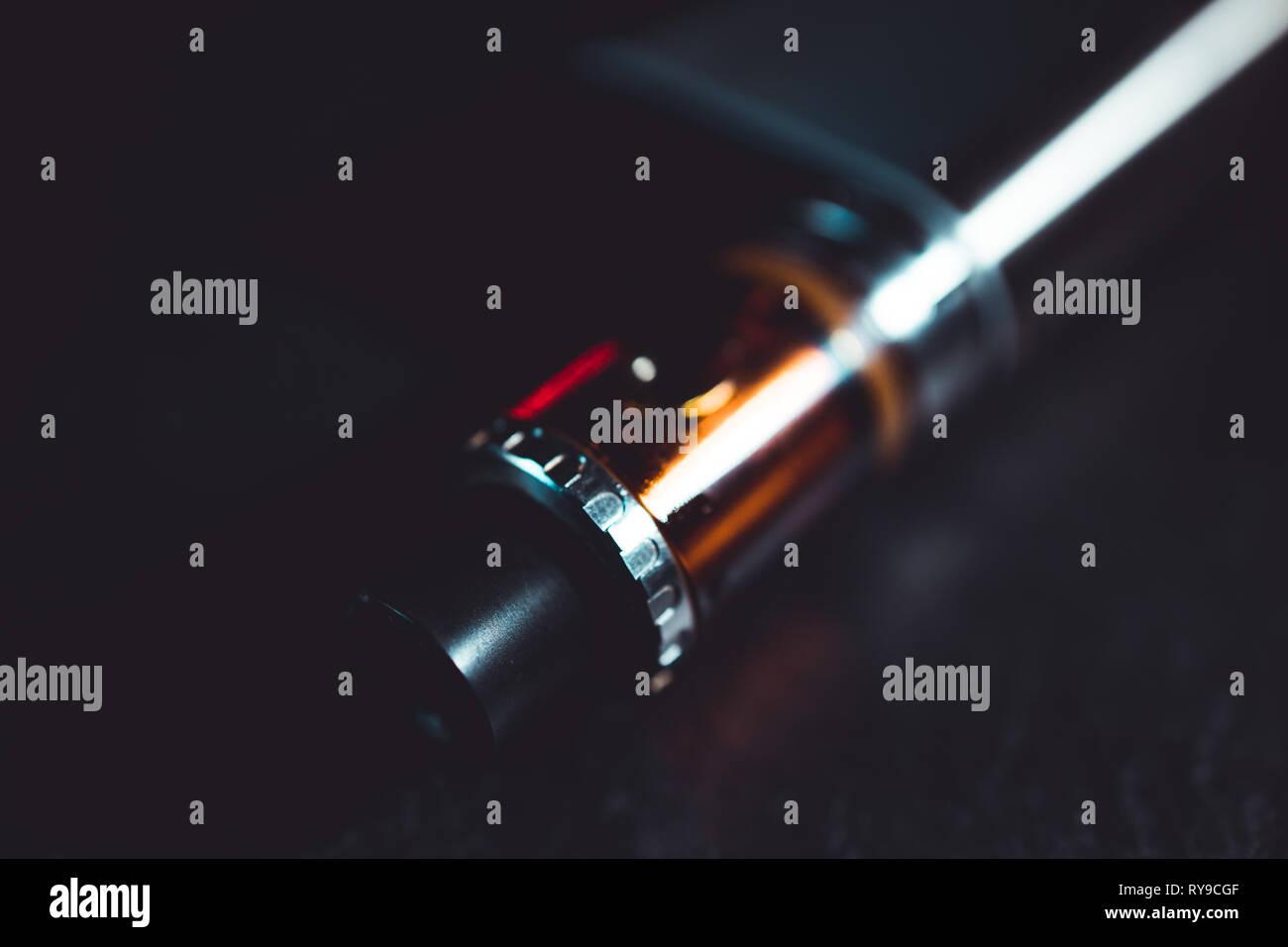 Vape pen metal electronic cigarette with vaping dark background - Stock Image
