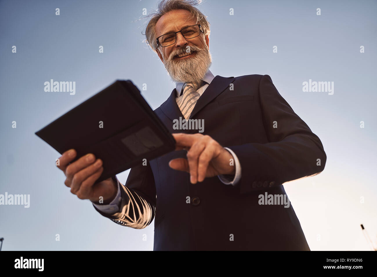 caucasian senior CEO using a smart tablet  - Stock Image