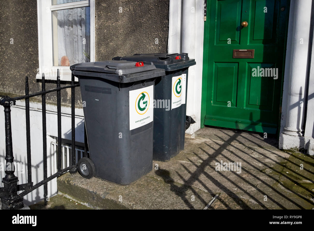 lockable private company wheelie bins outside a georgian house made into flats Dublin Republic of Ireland Europe - Stock Image