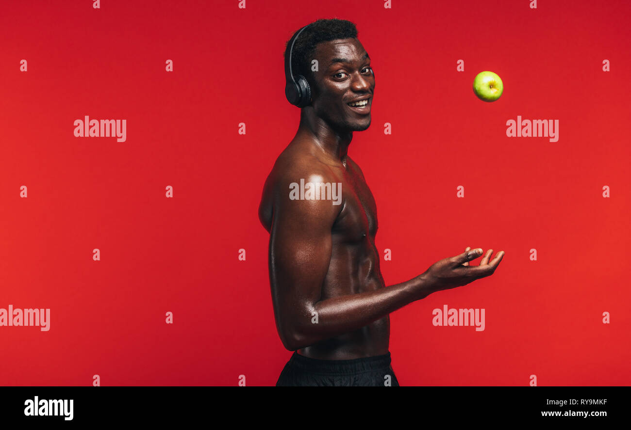 Confident young muscular man standing shirtless wearing headphones tossing up an apple against red background. - Stock Image