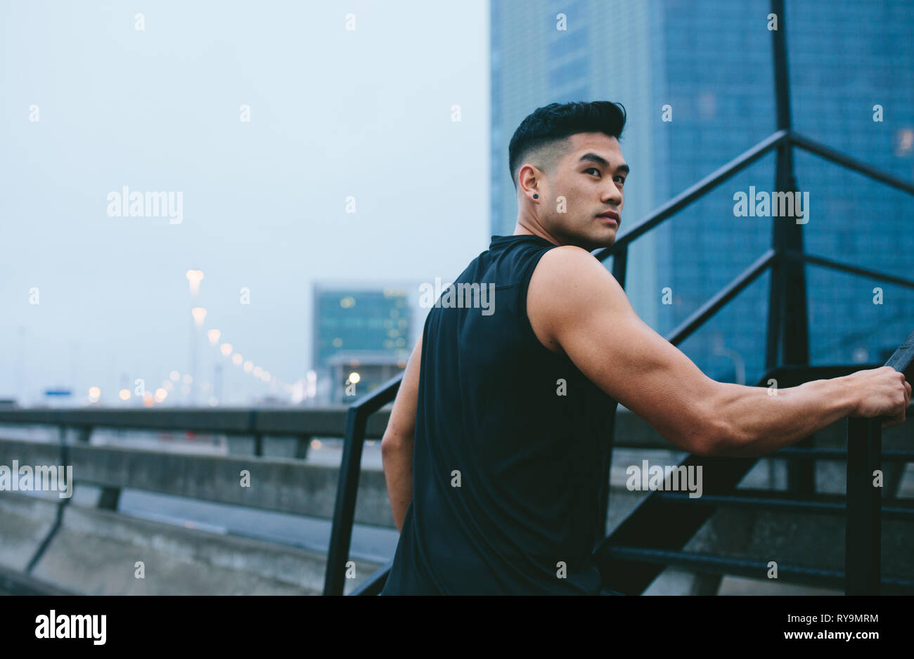 Man in walking up the stairs and looking away. Muscular man in sports clothing climbing up steps outdoors. - Stock Image