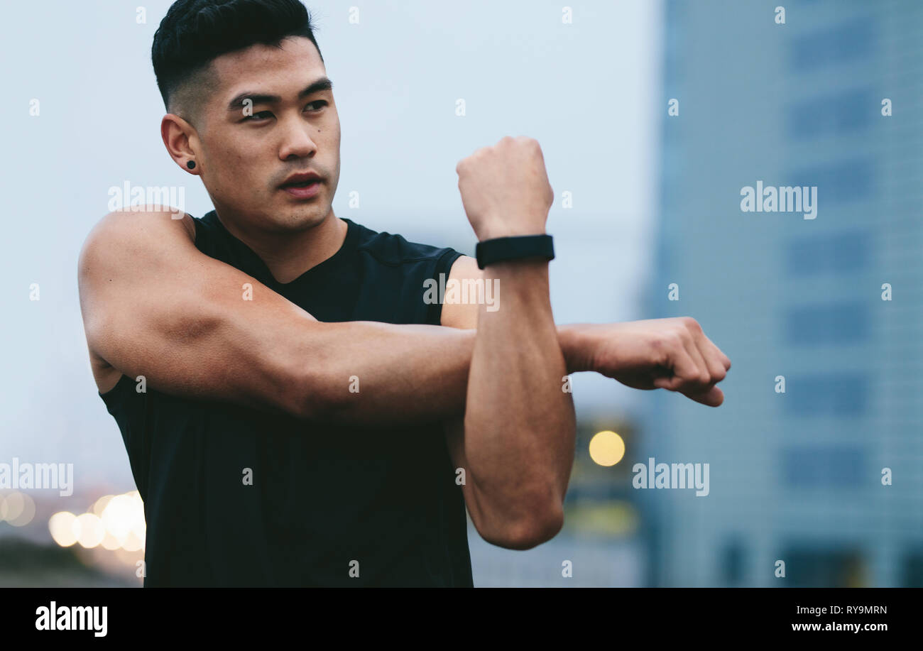 Fit young man with muscular build standing outside stretching hands and looking away. Asian fitness model doing warmup workout. - Stock Image