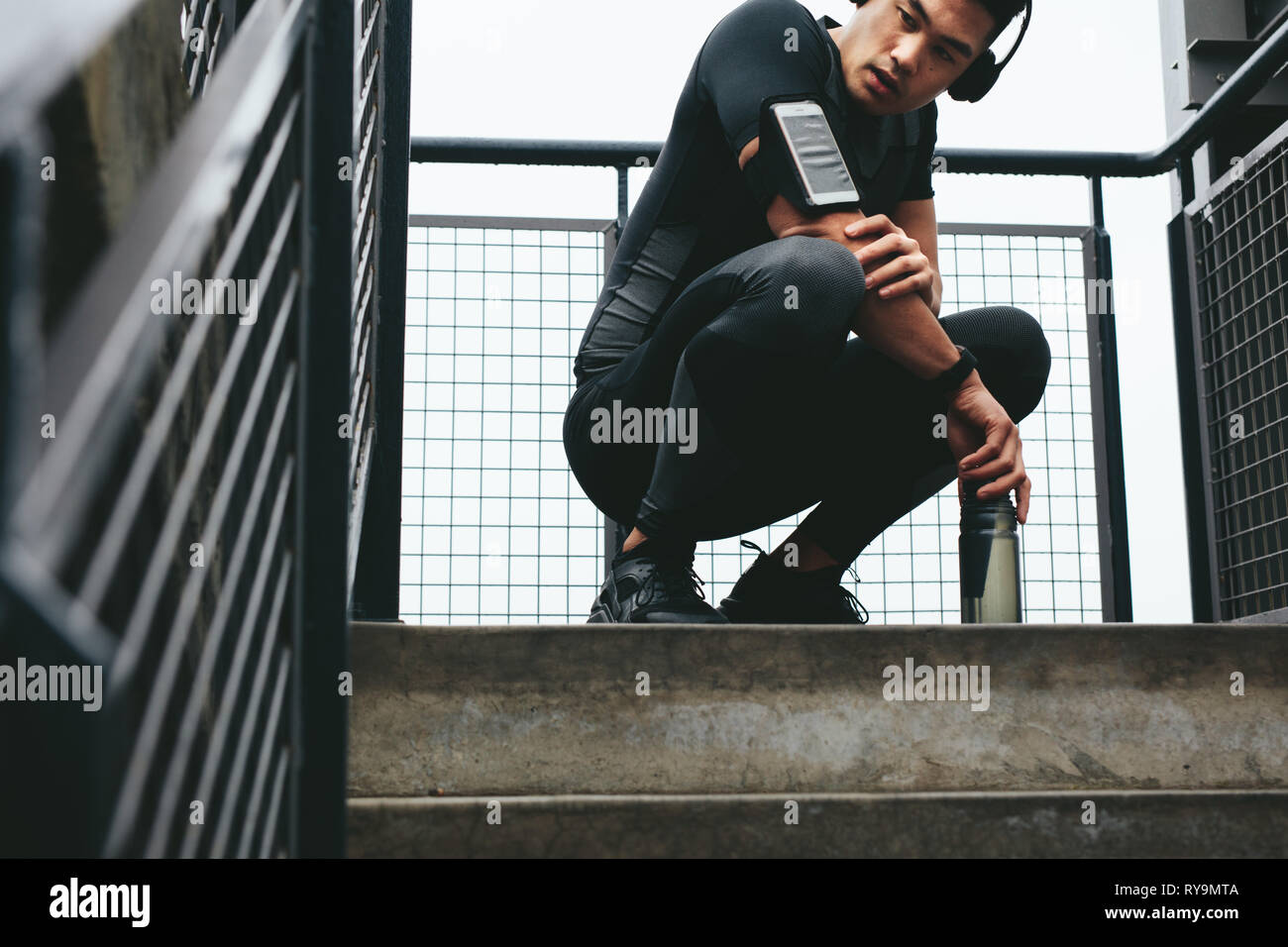 Young asian male listening to music on mobile phone. Fitness male with mobile phone armband crouching outdoors after exercising session. - Stock Image