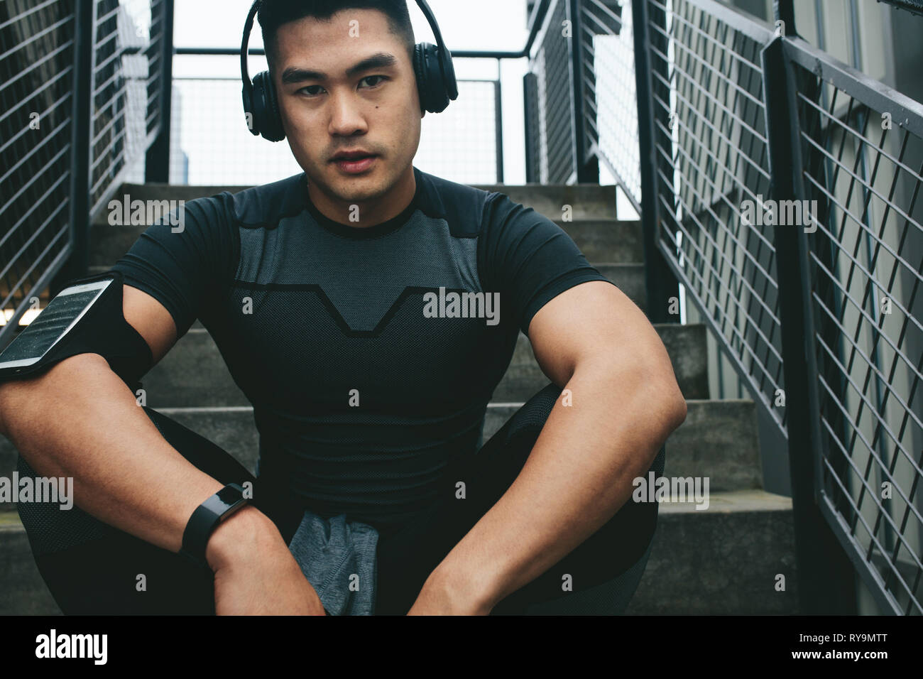 Portrait of asian man relaxing after workout sitting outdoors on stairs. Male athlete listening to music using wireless headphones while relaxing afte - Stock Image