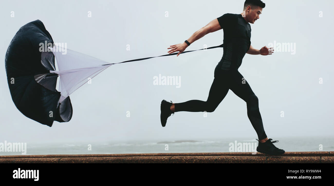 Strong man doing workout using resistance parachute outdoors. Young asian man in black sports clothing running with parachute. - Stock Image