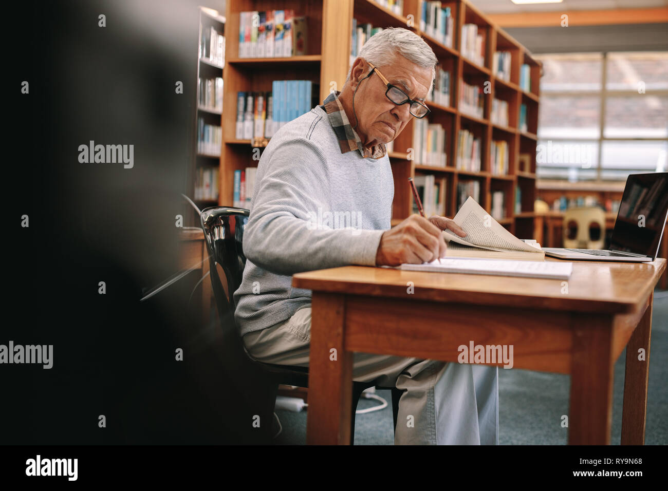 Senior man studying in classroom. Elderly man writing in a book sitting in classroom with a laptop in front. Stock Photo