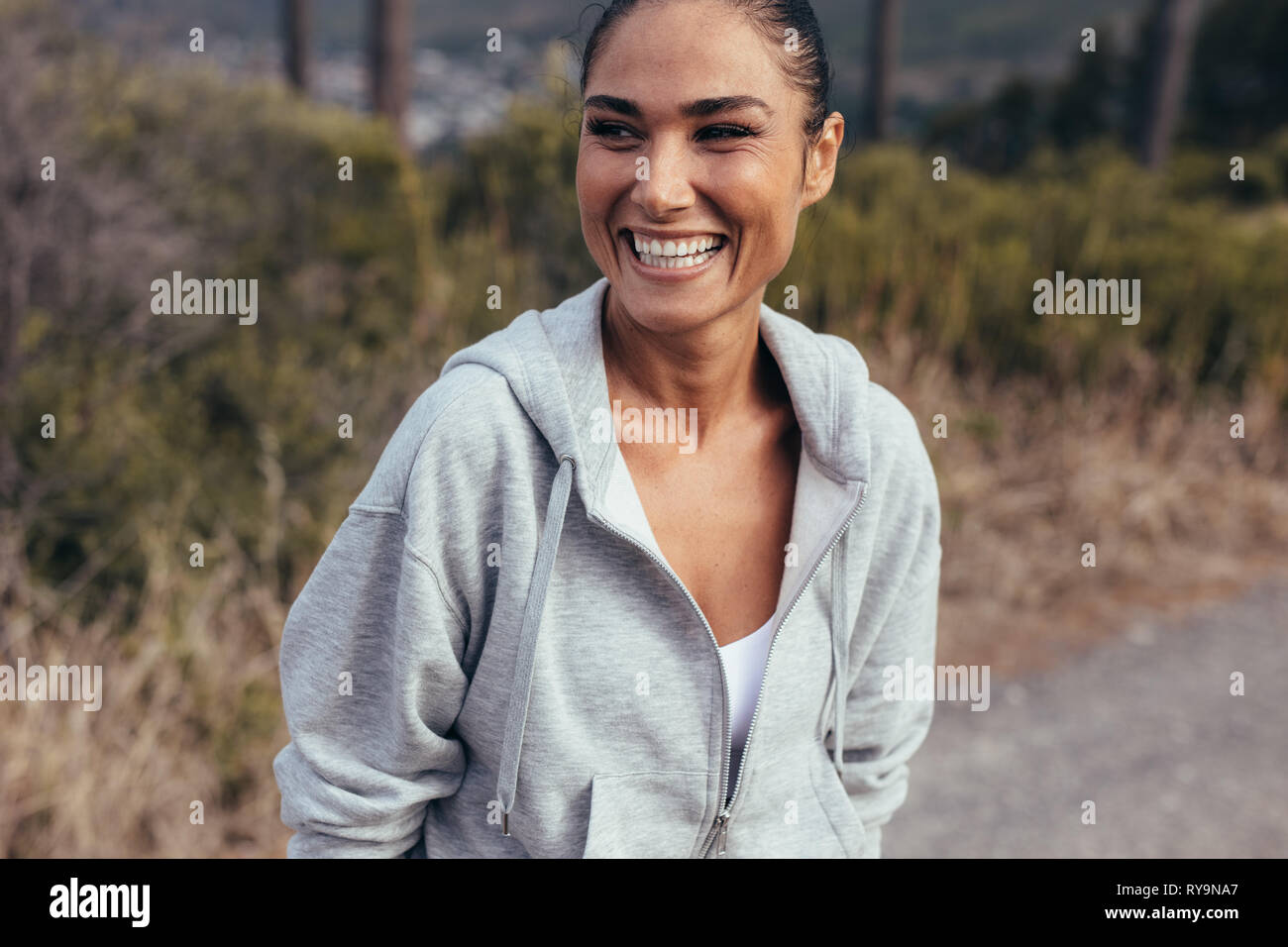 Cheerful female athlete standing outdoors during her morning fitness training. Woman in fitness wear taking a break after a morning run. Stock Photo