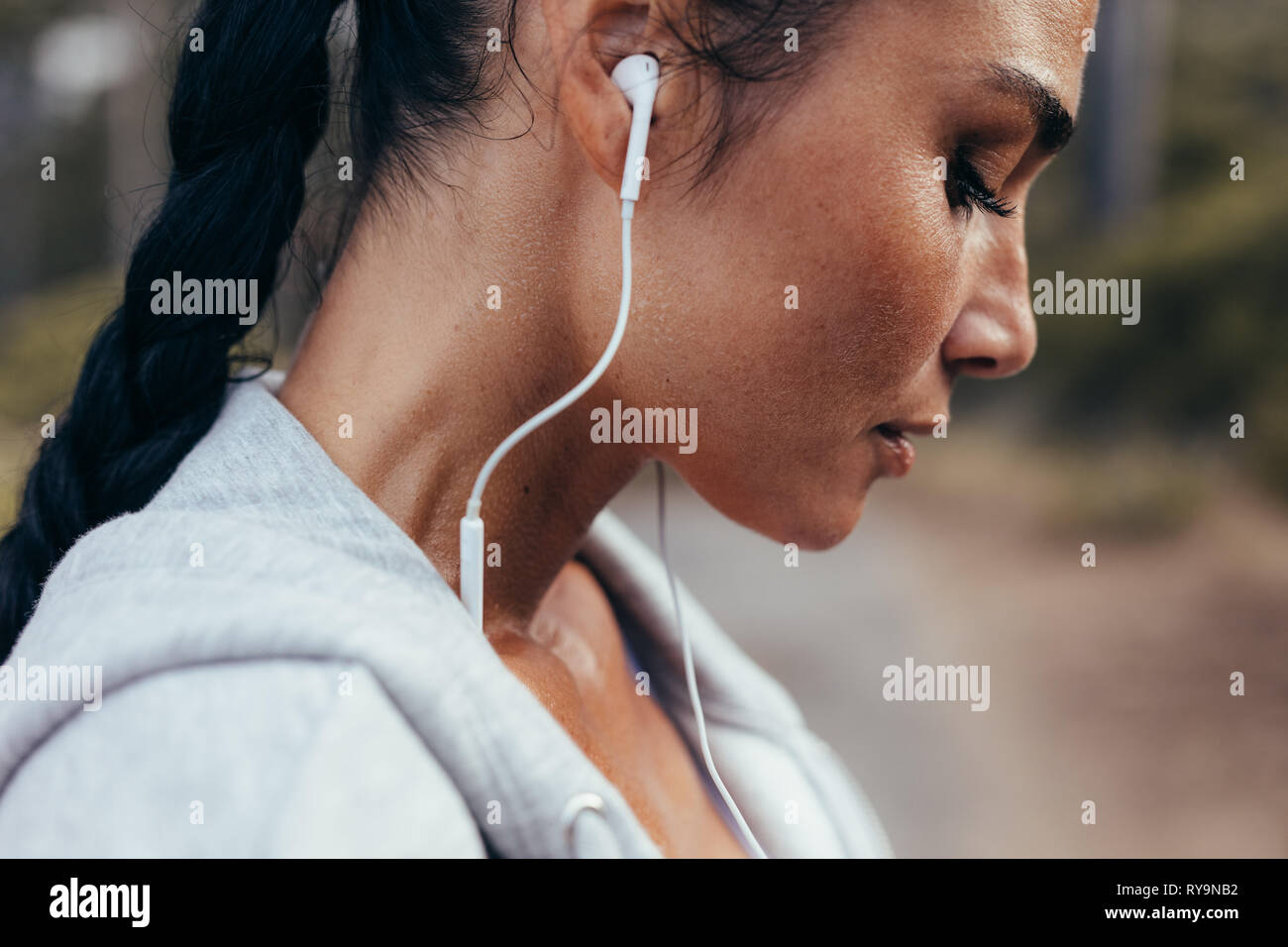 Close up of runner with sweat standing outdoors after her workout. Tired fitness female with earphones resting after exercising outdoors. - Stock Image