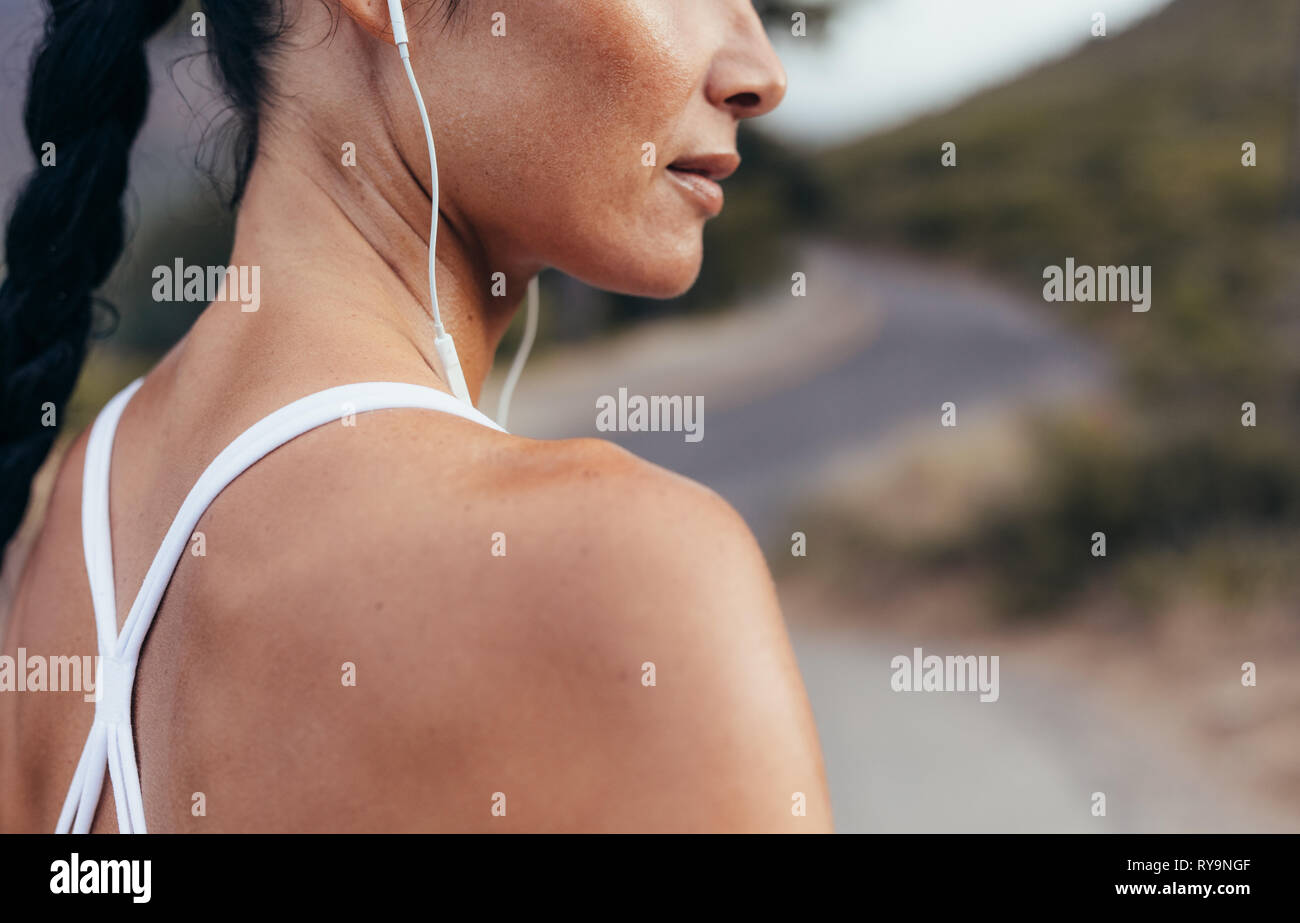 Side view of a woman athlete with earphones working out outdoors. Woman listening to music during workout outdoors in morning. - Stock Image