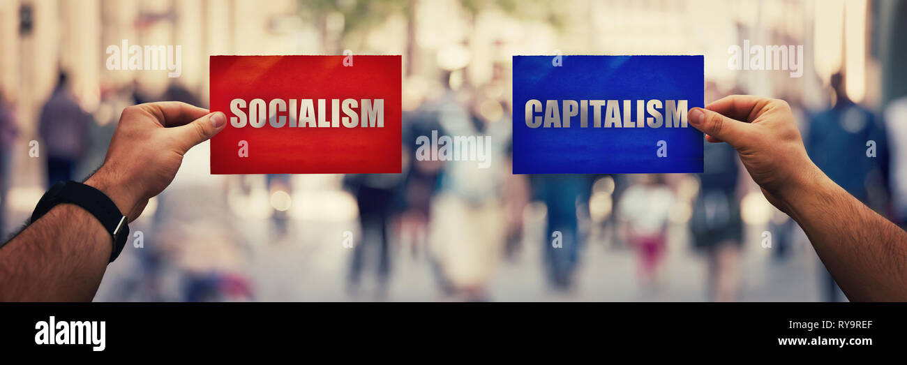 Two hands holding different colored paper sheet as socialist centralized economic planning versus capitalist liberated free market over crowded street - Stock Image