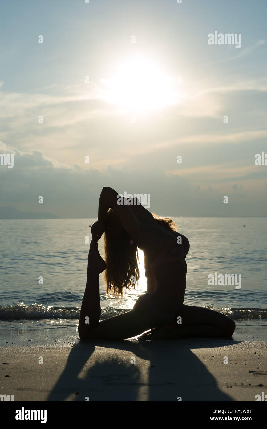 Girl's silhoutte behind Andaman sea and sun, practicing beach yoga at sunrise in Thailand Stock Photo