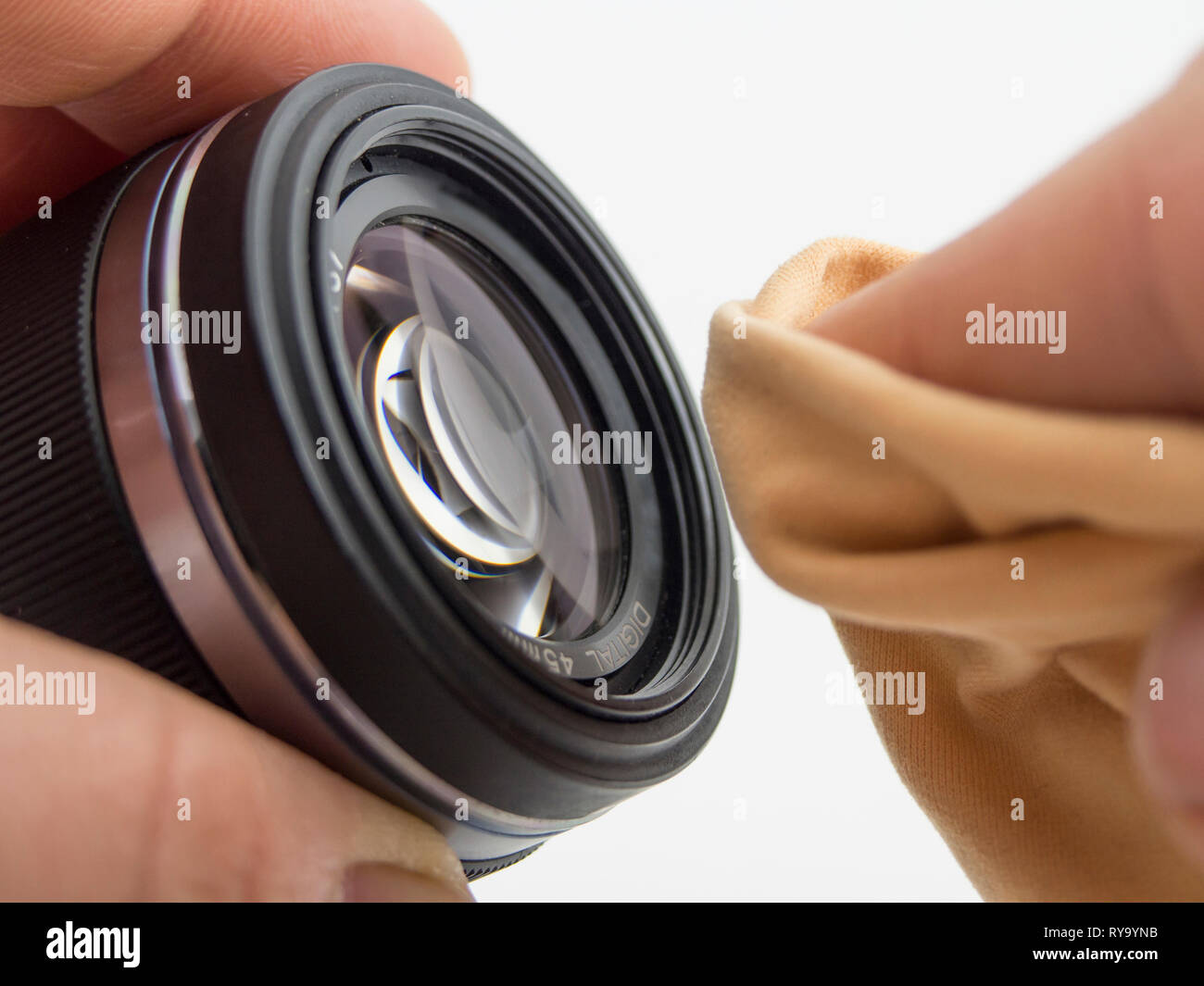 mirrorless system camera lens cleaning. person is cleaning the lens with a cloth - Stock Image