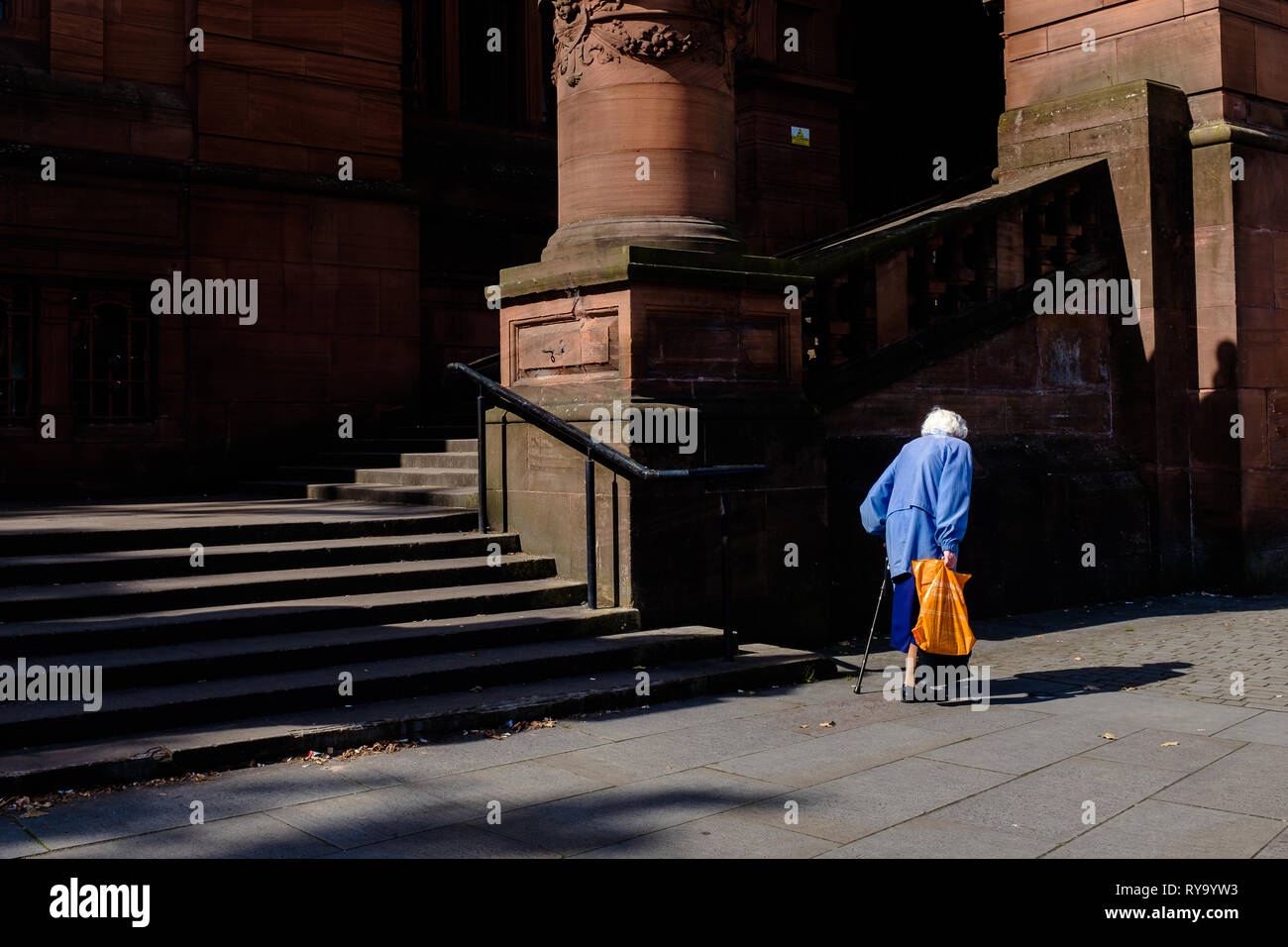 Old woman carrying shopping with stick seen from behind walking past Kelvingrove museum Glasgow Scotland uk - Stock Image