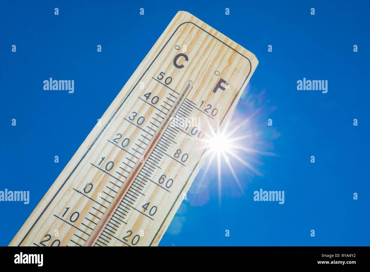 Ein Thermometer vor der gleissenden Sonne am blauen Himmel Stock Photo