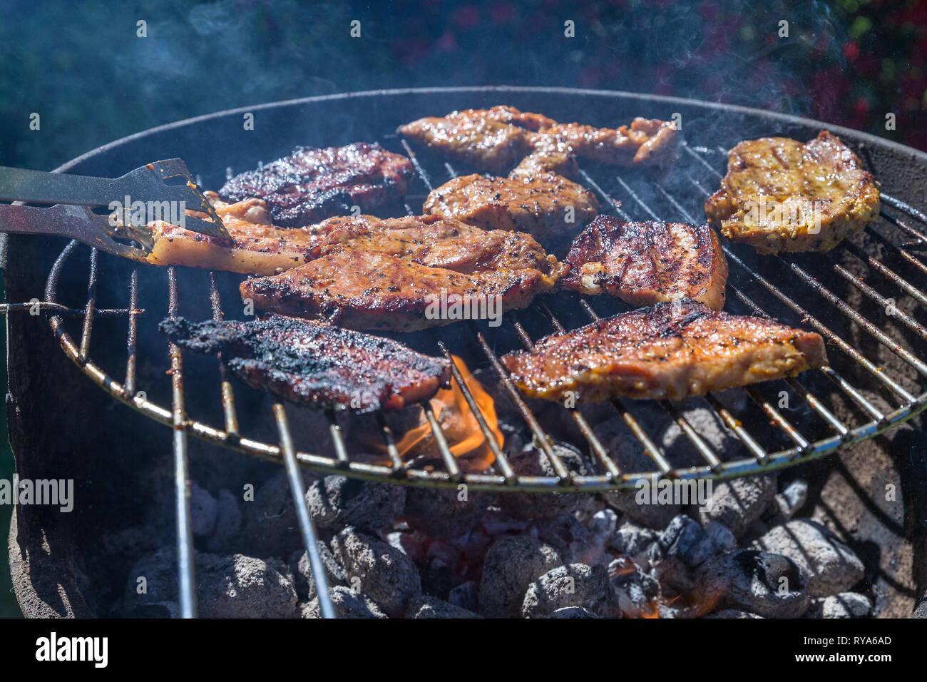 Bauchfleisch und Wuerstchen auf dem Grill, unter dem Grill lodern die Flammen bei THEMENBILD Grillen, 06.05.2018 Foto: Mario Hommes - Stock Image