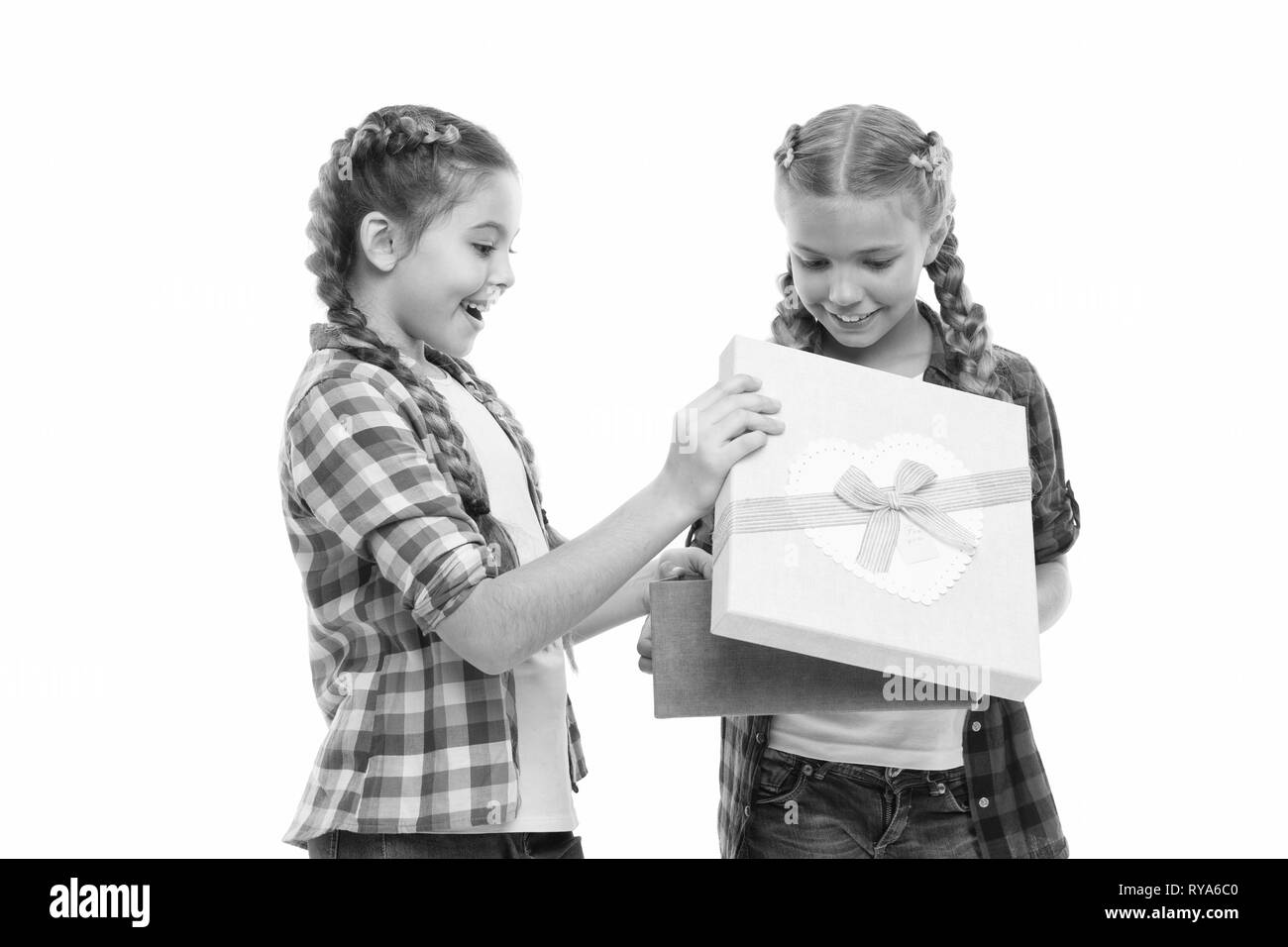 Kids little girls with braids hairstyle hold gift box. Children excited about unpacking gift. Small cute girls sisters received holiday gift. Dreams c - Stock Image