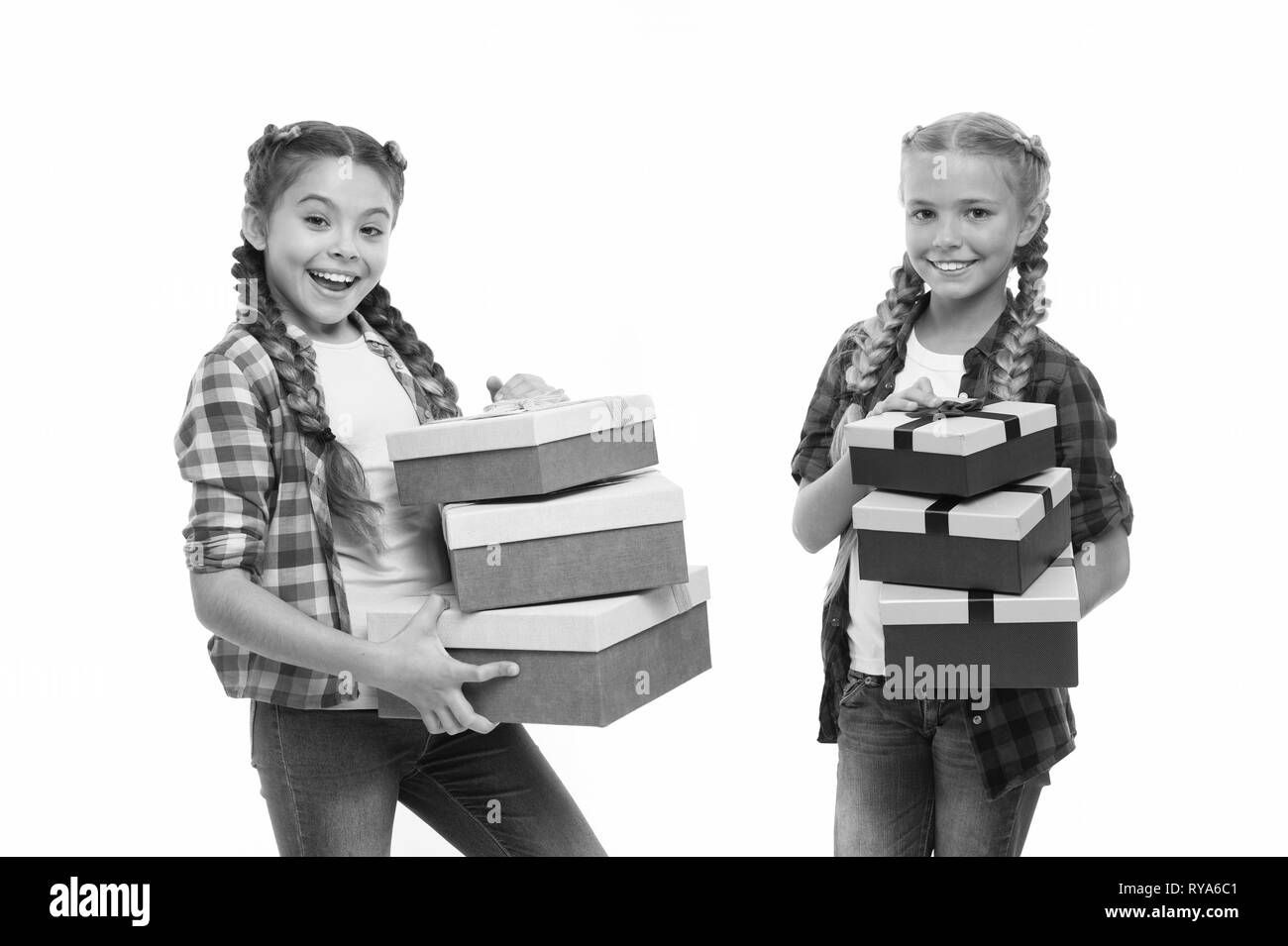 Kids little girls with braids hairstyle hold piles gift boxes. Children excited about unpacking gifts. Small girls sisters received birthday gifts. Dr - Stock Image