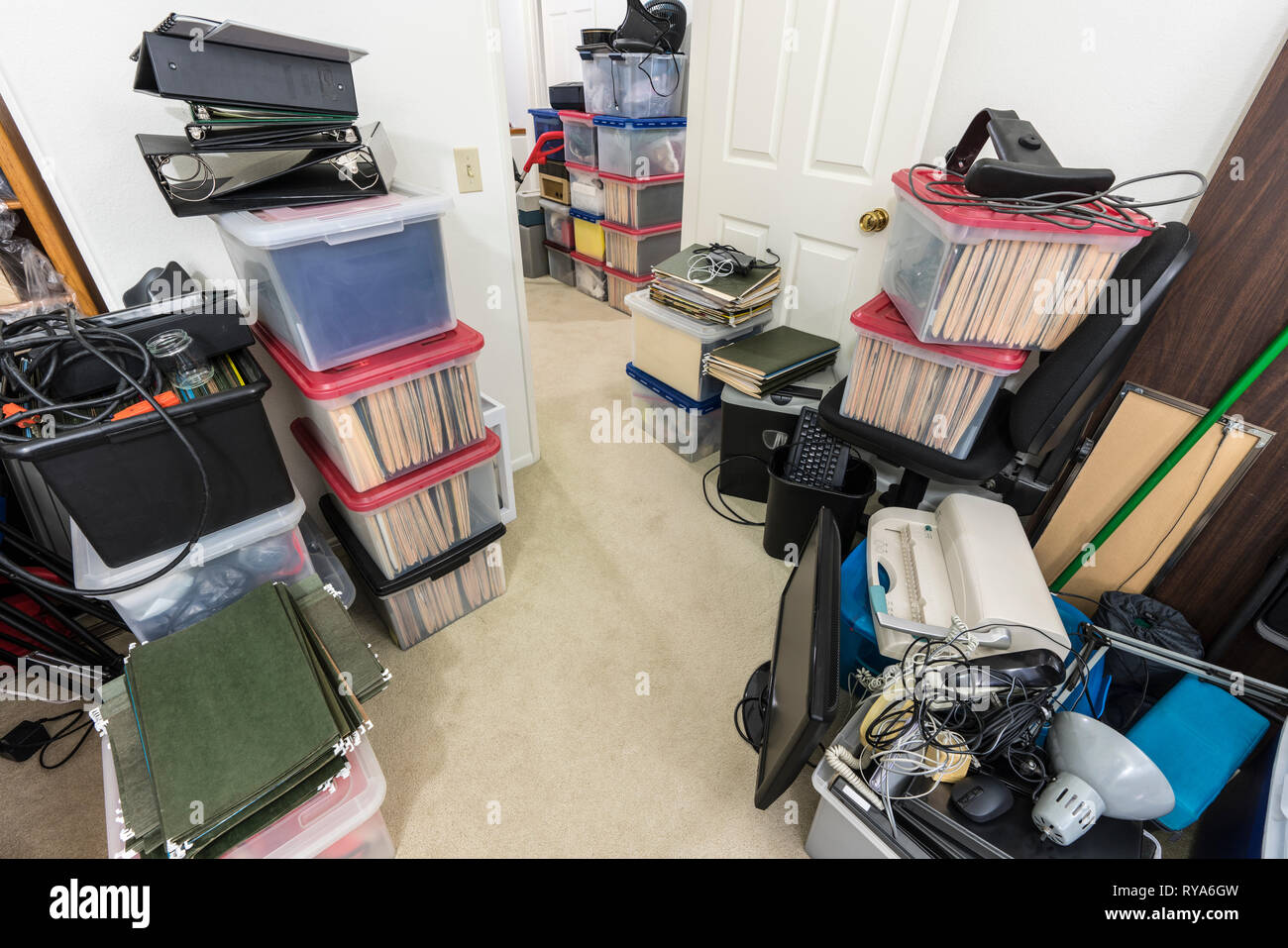 Messy office storage area with boxes, files, old equipment and miscellaneous clutter. - Stock Image