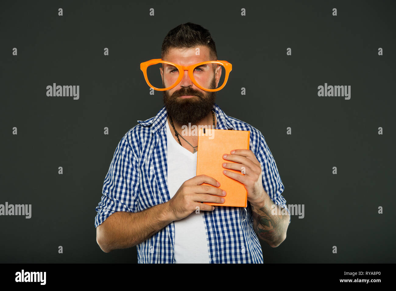 Geek is chic. Study nerd holding book. University male student with lecture notes. Book nerd wearing fancy glasses. Bearded man in party glasses with  - Stock Image