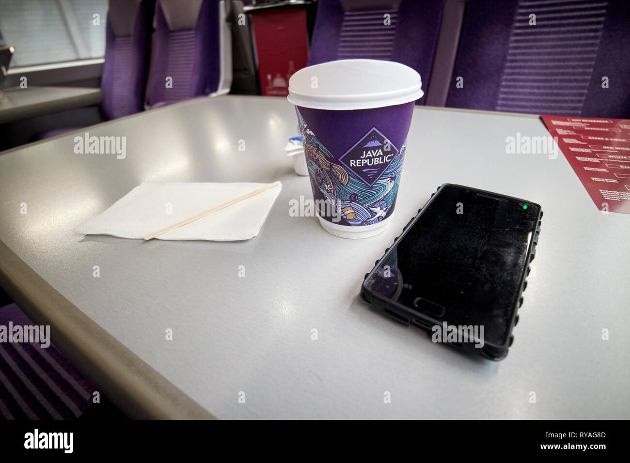 coffee and smartphone on enterprise train between Belfast and Dublin crossing the republic of Ireland northern ireland border - Stock Image
