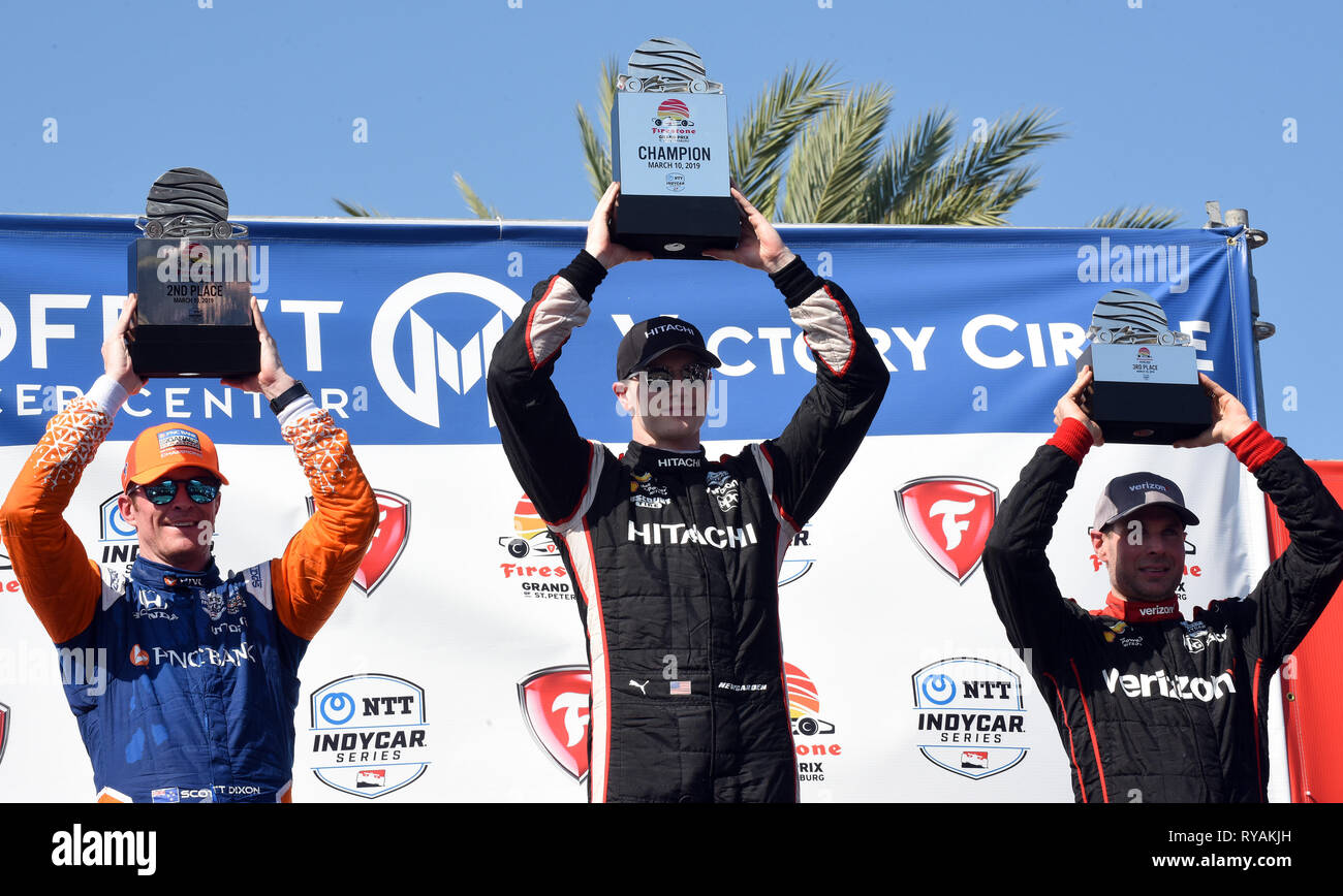 March 10, 2019 - St. Petersburg, Florida, United States - Firestone Grand Prix of St. Petersburg winner Josef Newgarden of the United States (center) holds a trophy over his head along with Scott Dixon of New Zealand (left) and Will Power of Australia (right) who took second and third-places respectively on March 10, 2019 in St. Petersburg, Florida. (Paul Hennessy/Alamy) - Stock Image