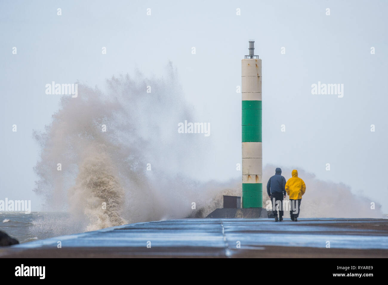 Aberystwyth, UK. 13th Mar, 2019. UK Weather: Young men take risks to get dramatic photographs of themselves close to the waves as gale force winds from Storm Gareth - the third named storm of 2019 - hit Aberystwyth on the Cardigan Bay coast, West Wales UK on Wednesday afternoon. Gusts of up to 70 or 80mph are forecast in exposed Northern regions, with the risk of serious damage to property and severe disruption to travel and power services Photo Credit: keith morris/Alamy Live News - Stock Image