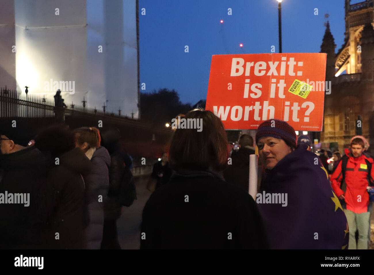 Brexit: is it worth it? - A Pro-remain demonstrator discusses Brexit outside the Houses of Parliament on the evening of the Meaningful Vote on Brexit. - Stock Image