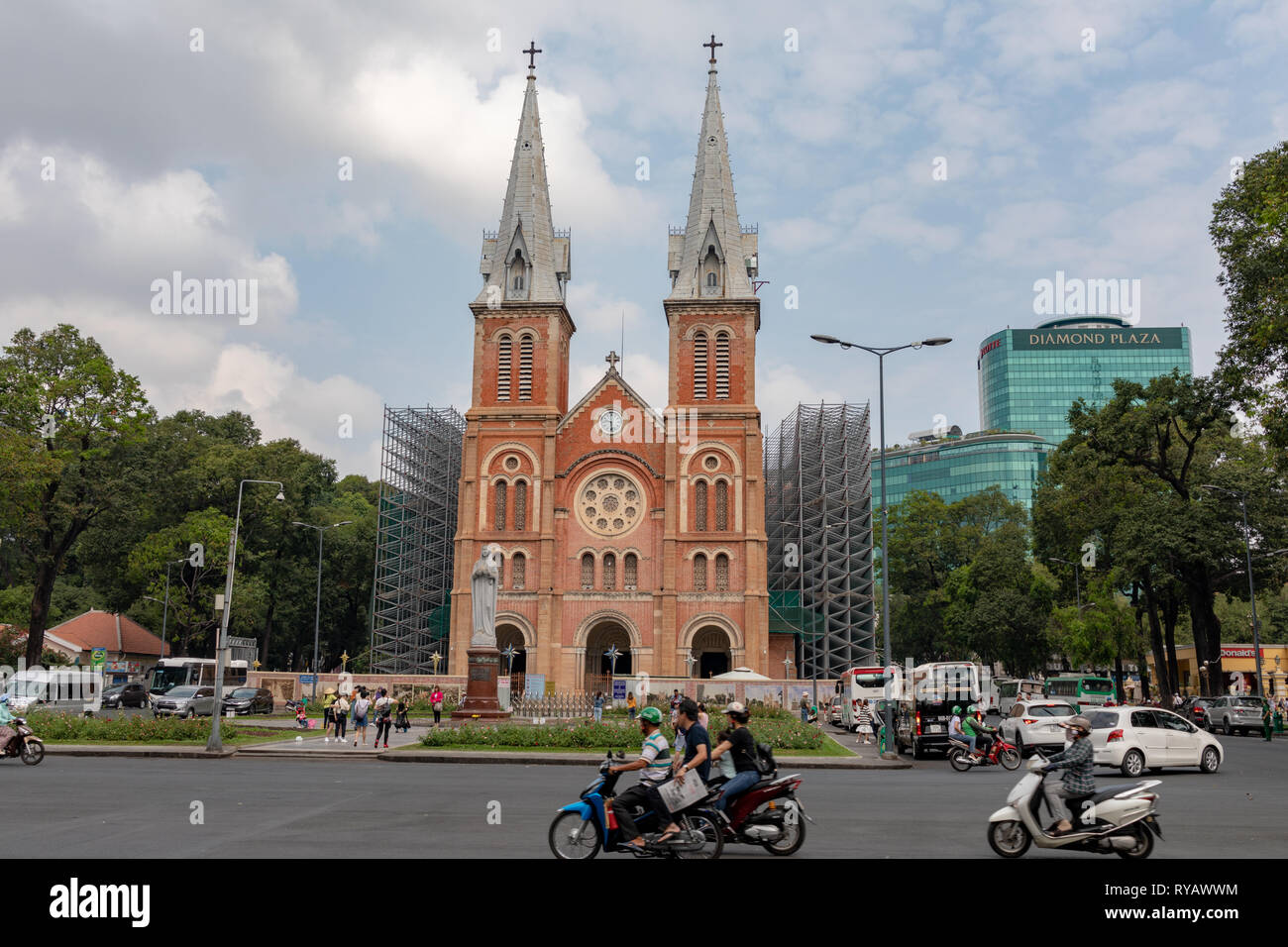 District 1 ,Ho Chi Minh City, Vietnam, Wednesday 13th March 2019.  Saigon weather::Hot spring day with highs of 36 degrees. Saigon Notre-Dame Basilica was constructed from 1863-1880 during the French colonial occupation of Vietnam. The cathedral displays distinct neo-Romanesque features, such as the two giant bell towers (holding six bronze bells), ornate stained glass windows, and a red brick facade that fascinated locals during its construction. The bricks were imported from Marseilles and were incredibly unique during that time period. It was conferred a Basilica by the Vatican in 1959 and  - Stock Image